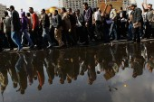 A crowd of anti-government protesters walk past a large puddle of water from tapped water mains in Tahrir Square on the morning of January 31, 2011 in central Cairo, Egypt [Chris Hondros/Getty Images]