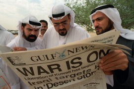 Kuwaiti exiles read a local newspaper announcing the start of the Gulf War in Dubai in this January 17, 1991 file photo. Thousands of Kuwaitis fled their country in 1990 after it was invaded by Iraqi forces. [File: Greg Bos/Reuters]