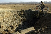 A Kashmiri boy with a bicycle walks past a crater caused by a landmine blast, in a photo from December 2004 [File: Reuters]