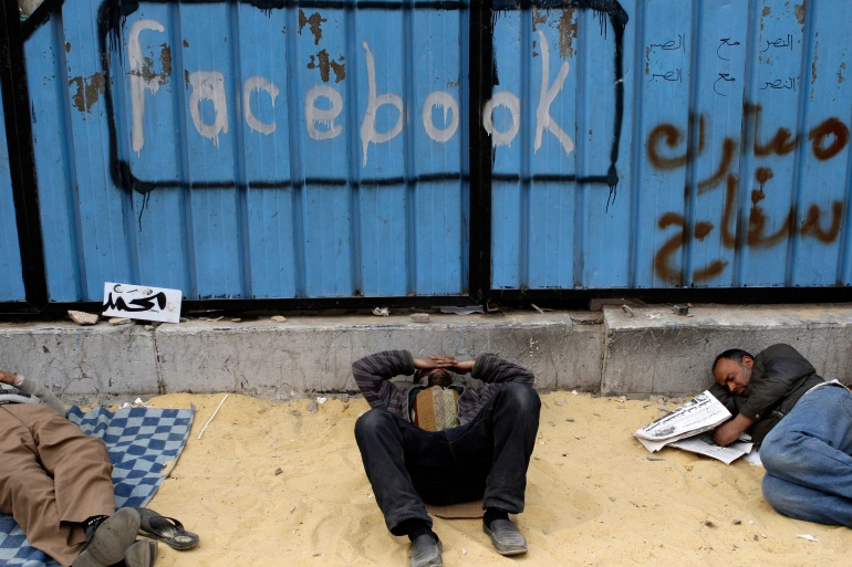 Opposition supporters rest near graffiti referring to social networking site 'Facebook' in Tahrir Square in Cairo on February 5, 2011 [File: Reuters/Steve Crisp]