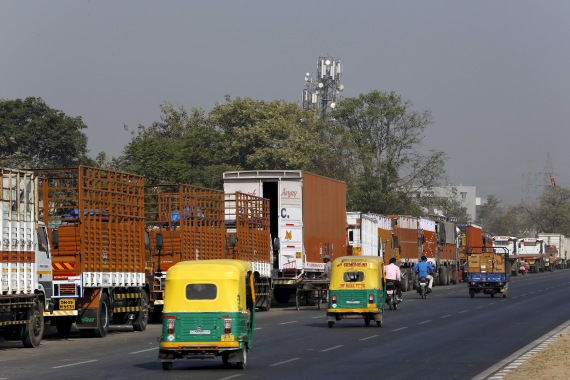 Auto rickshaws move past parked trucks along a national highway on the outskirts of Ahmedabad, Gujarat [File: Amit Dave/Reuters]
