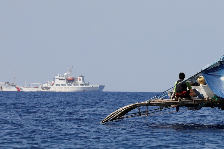 A Philippine fisherman watches a China Coast Guard vessel patrolling the disputed Scarborough Shoal [File: Erik De Castro/Reuters]