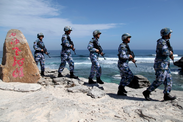 Soldiers of China's People's Liberation Army (PLA) Navy patrol at Woody Island, in the disputed Paracel islands. China plans to hold military exercises in the South China Sea this week [File: Stringer/Reuters]