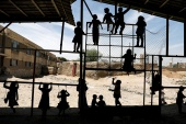 Internally displaced Afghan children play outside their shelter in Kabul [File: Mohammad Ismail/Reuters]