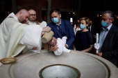 Marcin Jeziorek, wearing a protective mask, holds his baby, Mikolaj during a baptism ceremony, following the outbreak of the coronavirus disease (COVID-19), at church of the Monastery of St Joseph in Warsaw, Poland on May 30, 2020 [Kacper Pempel/Reuters]
