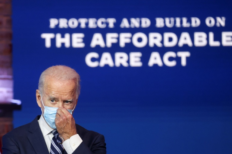 United States President Joe Biden adjusts his face mask after a brief news conference, where he discussed healthcare and the Affordable Care Act during his transition on November 10, 2020 [File: Jonathan Ernst/Reuters]