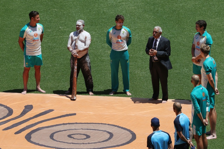 Cricket teams line up during a ceremony honouring Indigenous Australians before a match between Australia and India in Sydney [File: Loren Elliott/Reuters]