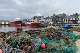 A view of fishing boats and a net in the coastal town of Macduff, Aberdeenshire, Scotland, October 18, 2020 [File: Alexander Smith/Reuters]