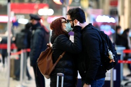 People wearing protective face masks kiss at Milan's Centrale railway station before travelling out of the city, before the tight restrictions on movement during the Christmas period put in place as part of efforts to curb the spread of COVID-19, in Milan, Italy, December 20, 2020 [Flavio Lo Scalzo/Reuters]