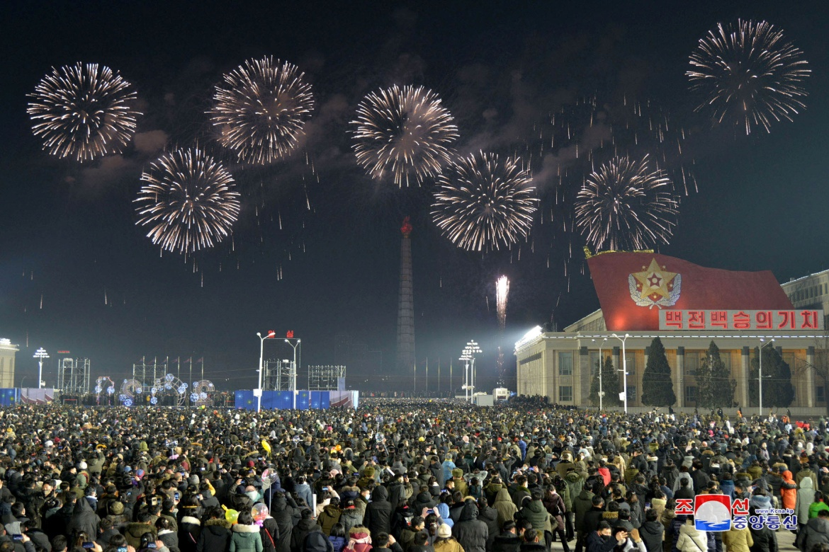 Fireworks explode over Pyongyang during New Year's celebrations in the North Korean capital. The country says it has had no cases of coronavirus but most in the crowd wore masks [Korean Central News Agency/via Reuters]
