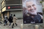 People walk near a photo of Iranian General Qassem Soleimani on the one year anniversary of his assassination by a US drone, in Tehran on January 1, 2021 [Majid Asgaripour/WANA via Reuters]