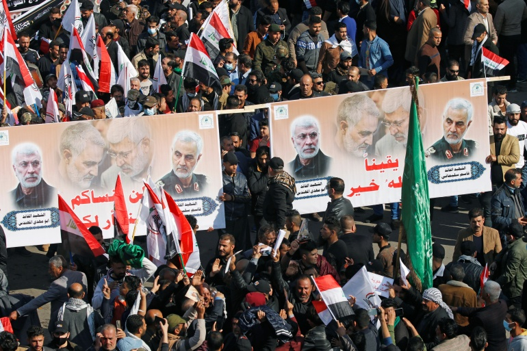 Iraqis hold placards depicting Soleimani and al-Muhandis as they mark the first anniversary of their deaths in Baghdad [Khalid Al-Mousily/Reuters]