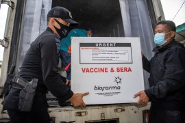Officers offload a box of Sinovac's vaccine for COVID-19 as it arrives at the cold room of Indonesia's local health department in Palembang, South Sumatra province, Indonesia, January 4, 2021 [Antara Foto/Nova Wahyudi/ via Reuters]
