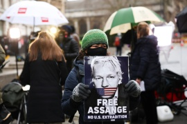 A supporter of WikiLeaks founder Julian Assange holds a placard at the Old Bailey, the Central Criminal Court in London, on January 4, 2021 [Henry Nicholls/ Reuters]