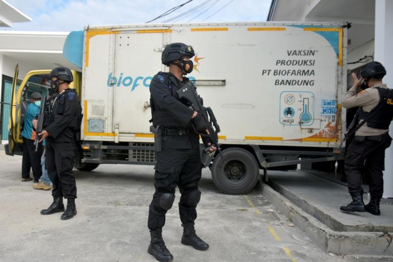 Petugas polisi bersenjata berjaga di samping truk berisi vaksin Sinovac di Pekanbaru, provinsi Riau, Indonesia [Antara Foto / FB Anggoro via Reuters]