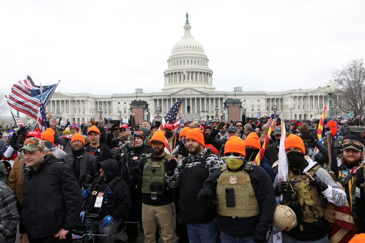 """Members of the far-right group Proud Boys make 'OK' hand gestures indicating """"white power"""" as supporters of US President Donald Trump gather in front of the US Capitol Building to protest against the certification of the 2020 presidential election results by the US Congress. [Jim Urquhart/Reuters]"""