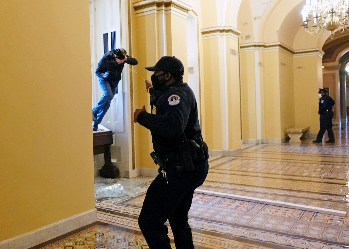 A US Capitol police officer shoots pepper spray at a protestor attempting to enter the Capitol building during a joint session of Congress to certify the 2020 election results. [Kevin Dietsch/Pool via Reuters]