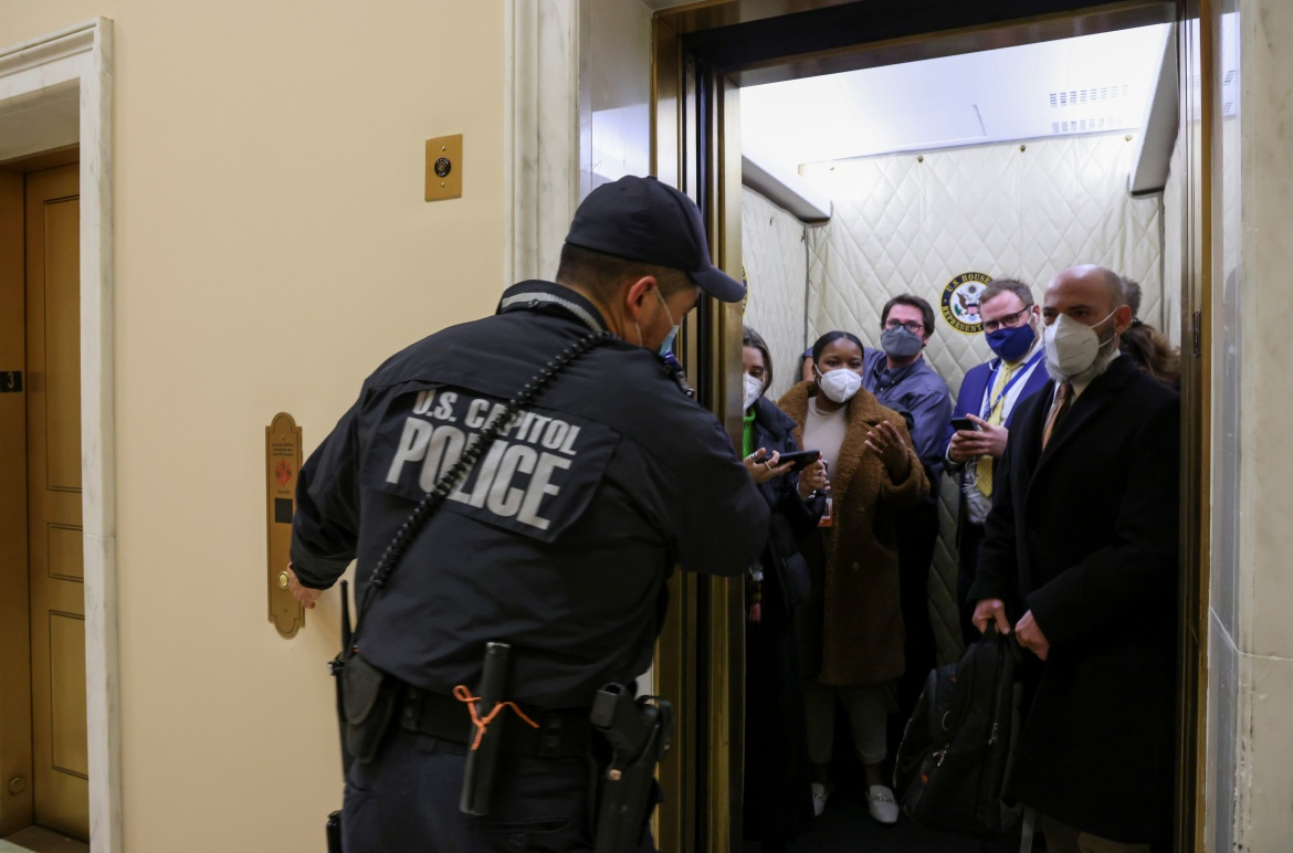 US Capitol Police evacuate journalists and House press staff members from the Capitol to a connected office building. [Jonathan Ernst/Reuters]