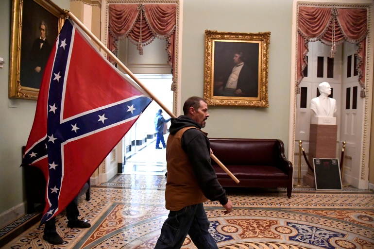 A supporter of President Donald Trump carried a Confederate flag into the Senate wing of the US Capitol building on January 6 [Mike Theiler/Reuters]