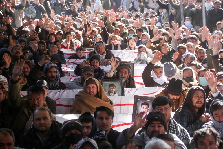 People chant slogans as they sit with coffins of their relatives, coal miners from the Shia Hazara minority killed in an attack [Naseer Ahmed/Reuters]