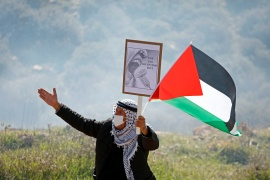 A demonstrator holds a banner and Palestinian flag during a protest against the building of illegal Israeli settlements in Beit Dajan in the Israeli-occupied West Bank on January 8, 2021 [Raneen Sawafta/Reuters]