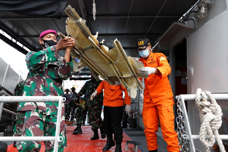 Indonesian rescue workers carry debris of Sriwijaya Air flight SJ-182, which crashed into the sea [Willy Kurniawan/Reuters]