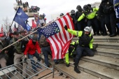 Members of US Capitol Police try to fend off a mob of supporters of US President Donald Trump as they storm the US Capitol, January 6, 2021 [Leah Millis/Reuters]