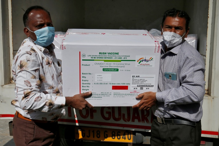 Officials unload boxes containing vials of Covishield vaccine outside a vaccination storage centre in Ahmedabad, India [Amit Dave/Reuters]