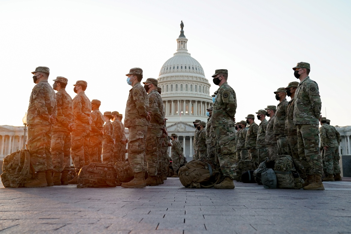 Members of the National Guard gather at the US Capitol as the House of Representatives prepares to begin the voting process on a resolution demanding US Vice President Pence and the cabinet remove President Trump from office, in Washington. [Erin Scott/Reuters]