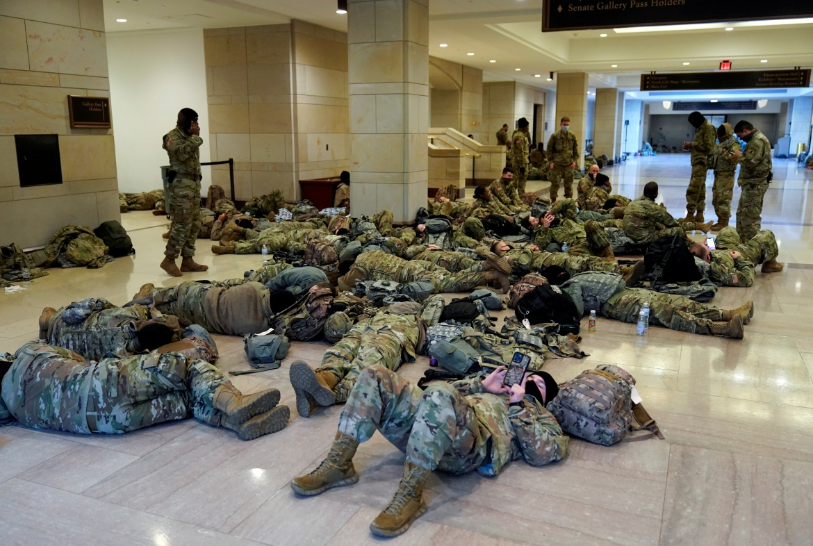 National Guard members sleep in the Capitol Vistor's Center on Capitol Hill before Democrats begin debating one article of impeachment against US President Donald Trump. [Joshua Roberts/Reuters]