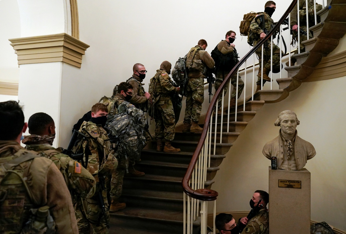 As legislators debated impeaching Trump, National Guard troops and police were stationed around the Capitol to provide security. [Joshua Roberts/Reuters]