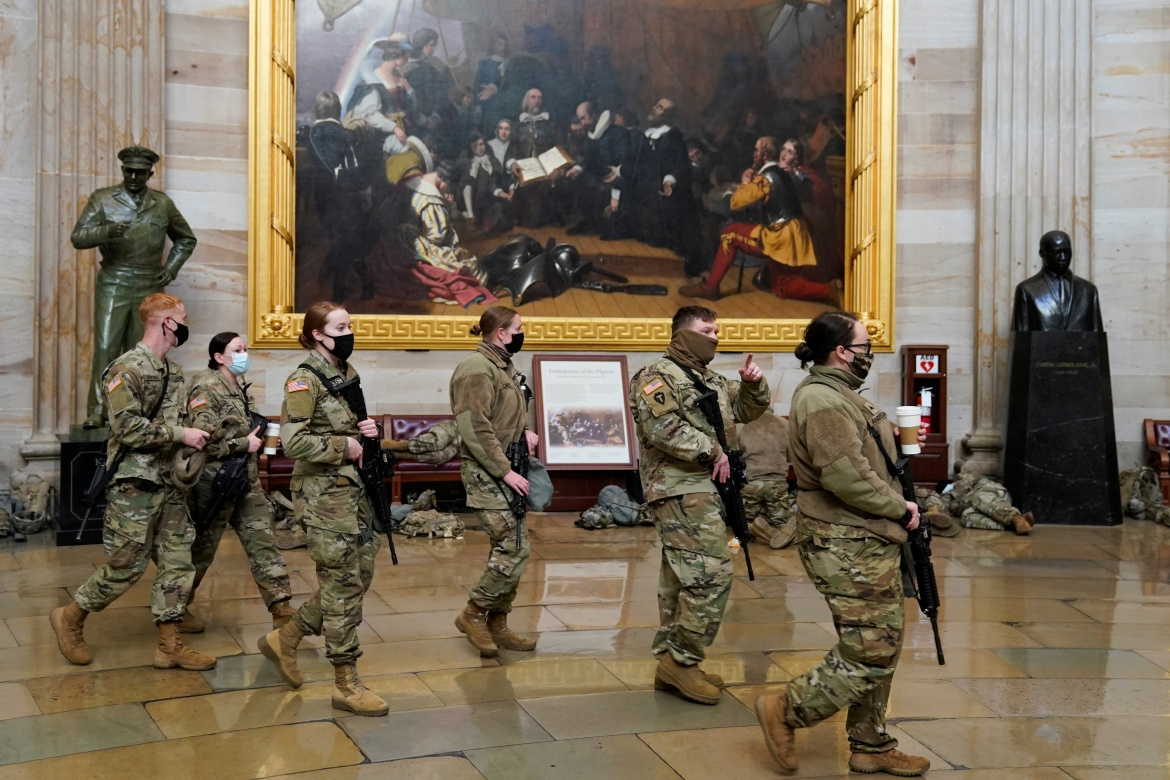 National Guard members walk through the US Capitol. [Joshua Roberts/Reuters]
