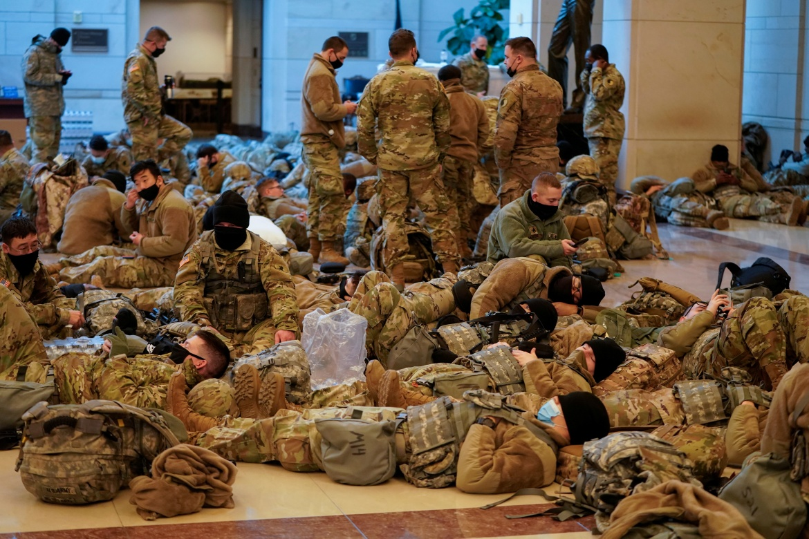 Thousands of National Guard troops were planned to be on hand and some members in fatigues, with weapons at hand, could be seen sleeping inside the Capitol building on Wednesday ahead of the session. [Joshua Roberts/Reuters]