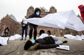 Front-line workers stage a 'die-in' protest to demand paid sick days for all workers, in front of the Ontario provincial legislature in Toronto, Ontario on January 13, 2021 [Carlos Osorio/Reuters]