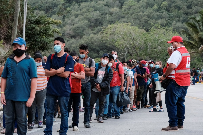 Hondurans taking part in a new caravan of migrants, set to head to the US, line up to receive water from the Red Cross after arriving to the El Florido border crossing point with Guatemala, in El Florido, Honduras [Yoseph Amaya/Reuters]