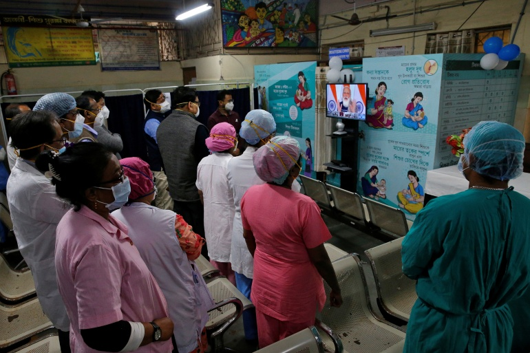 Healthcare workers listen as Indian Prime Minister Narendra Modi addresses them via video conferencing at a government-run hospital in Kolkata [Rupak De Chowdhuri/Reuters]
