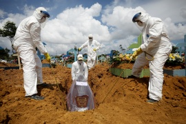 Gravediggers work during the burial of Jailton de Meneses, 43, who passed away due to COVID-19, at the Parque Taruma cemetery in Manaus, Brazil, on January 17 [Bruno Kelly/Reuters]