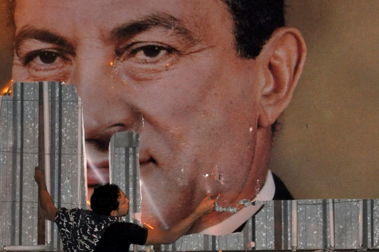 An anti-government protester defaces a picture of Egypt's President Hosni Mubarak in Alexandria on January 25, 2011 [File: Reuters/Stringer]