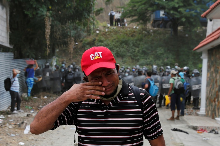 A Honduran man reacts after Guatemalan security forces cleared a road where migrants and asylum seekers have been camping after authorities halted their trek to the United States, in Vado Hondo, Guatemala [Luis Echeverria/Reuters]