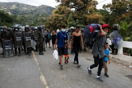 Honduran migrants walk towards El Florido border crossing point to return to their country after Guatemalan security forces halted their US-bound caravan this month [File: Luis Echeverria/Reuters]