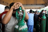 Relatives of patients hospitalised or receiving healthcare at home, who are mostly suffering from the coronavirus disease (COVID-19), gather to buy oxygen and fill cylinders at a private company in Manaus, Brazil January 18, 2021 [Bruno Kelly/Reuters]