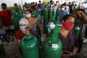 Relatives of patients hospitalised or receiving healthcare at home, who are mostly suffering from COVID-19, gather to buy oxygen and fill cylinders at a private company in Manaus [Bruno Kelly/Reuters]