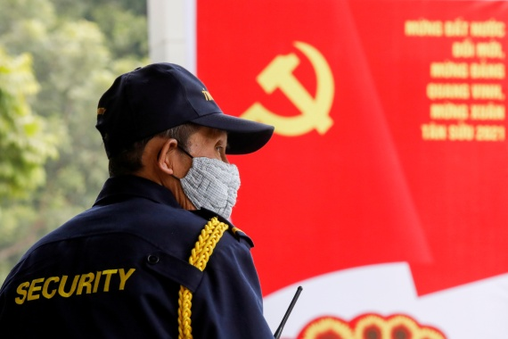 A security officer stands guard near a poster for the upcoming 13th National Congress of the ruling Communist Party of Vietnam, on a street in Hanoi, Vietnam January 12, 2021 [File: Kham/Reuters]