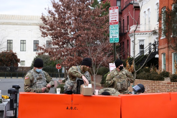 Members of the National Guard have coffee while standing watch at a barrier on a close street ahead of US President-elect Joe Biden's inauguration. [Caitlin Ochs/Reuters]