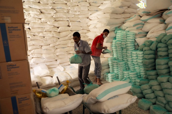 Workers prepare foodstuff for beneficiaries at a food distribution centre supported by the World Food Programme in Sanaa, Yemen on June 3, 2020 [File: Khaled Abdullah/Reuters]