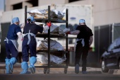 El Paso County Medical Examiner's Office staff move bodies in bags labelled 'COVID' from refrigerated trailers into the morgue office on November 23, 2020 [File: Ivan Pierre Aguirre/Reuters]
