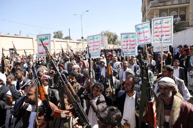 Houthi supporters hold up their weapons during a demonstration against the United States [Khaled Abdullah/Reuters]