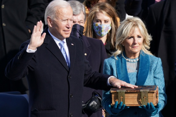 Joe Biden is sworn in as the 46th president of the United States on the West Front of the US Capitol in Washington, DC with his wife Jill Biden at his side. [Kevin Lamarque/Reuters]