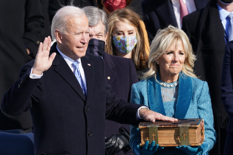 Joe Biden is sworn in as the 46th President of the United States as his wife Jill Biden holds a bible [Kevin Lamarque/Reuters]
