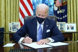 US President Joe Biden signs executive orders in the Oval Office of the White House in Washington, after his inauguration as the 46th President of the United States [Tom Brenner/Reuters]